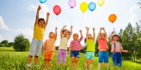 Happy kids with balloons and arms up in the sky in green field - УППЧ